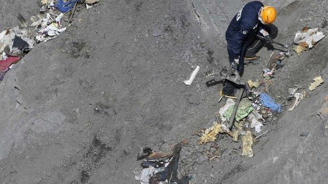 Rescue worker inspects crash site of flight 4U 9525