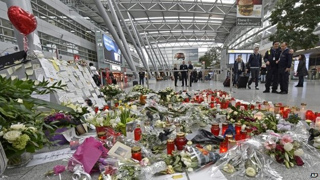 Passengers pass by candles and flowers for the victims of the plane crash at the airport in Dusseldorf (31 March 2015)