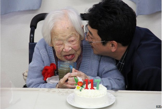 A handout picture provided by the Kurenai Nursing Home shows 117-year-old Japanese Misao Okawa (L) smiling before a birthday cake at the nursing home in Osaka, western Japan, 5 March 2015