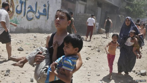 Palestinians run away from the scene of an air strike in Gaza City (9 July 2014)