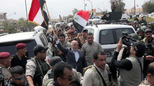 Iraqi Prime Minister Haider al-Abadi waves an Iraqi flag in Tikrit (1 April 2015)