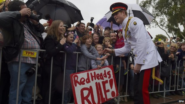 """Prince Harry meeting a crowd in Australia. A sign says """"red heads rule""""."""