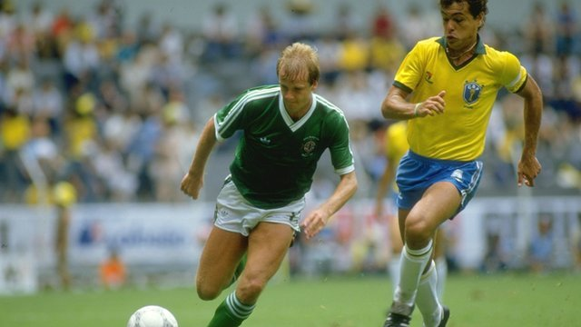 Northern Ireland striker Colin Clarke is tracked by Brazil's Edhino Ibra in the World Cup match