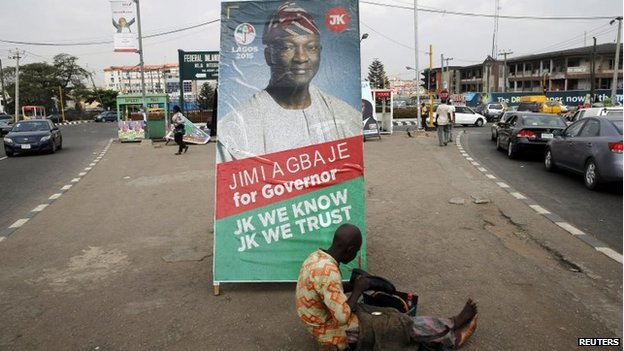 A shoe-mender works near a poster campaigning for frontline contender and Lagos governorship candidate for the People's Democratic Party (PDP)