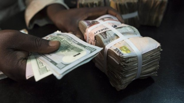 A trader changes dollars with naira at a currency exchange store in Lagos 12 February 2015