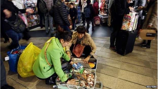 Mainland Chinese shoppers pack goods into suitcases in Hong Kong (9 Feb 2015)