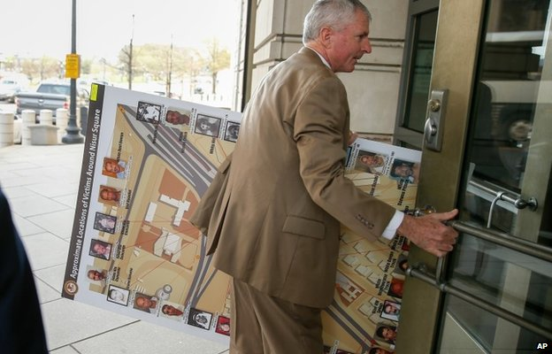 """A man carrying a poster that reads """"approximate locations of victims around Nisoor Square"""" enters the E. Barrett Prettyman Federal Courthouse in Washington"""