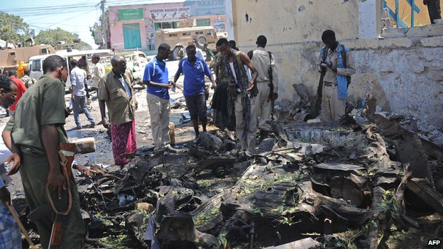 People look at the wreckage of a car bomb outside the higher education ministry in Mogadishu, Somalia on Tuesday