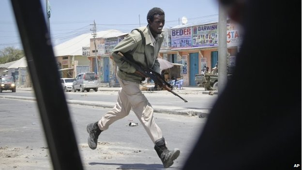 A Somali soldier runs during fighting following a car bomb that was detonated at the gates of a government office complex in Somalia's capital Mogadishu on Tuesday