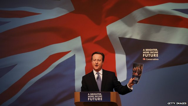 David Cameron holding up copy of Conservative manifesto at launch