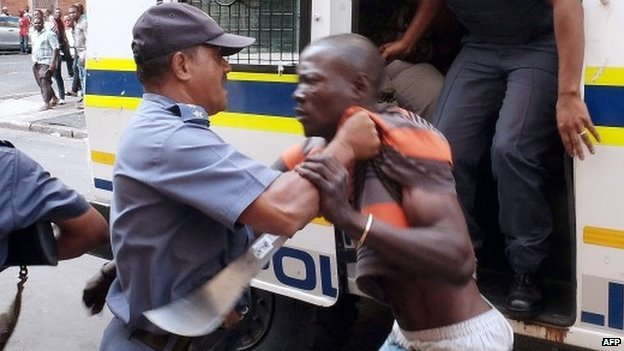 Members of the South African Police Services (SAPS) try to control a protester after clashes broke out between a group of locals and police in Durban on 14 April 2015