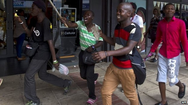 South African men run from police as rioting and looting was quelled during anti-foreigner violence in Durban 14 April 2015