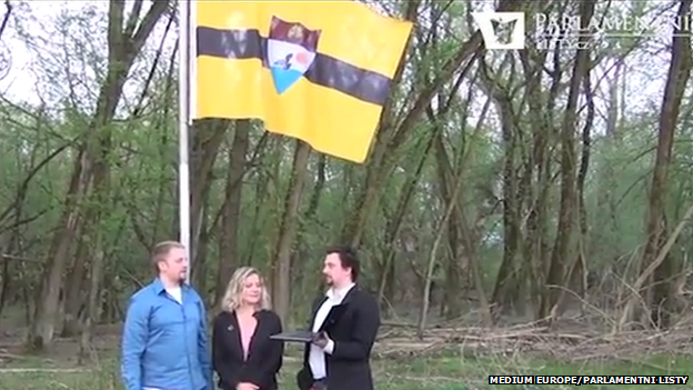"""The """"founders"""" of Liberland standing in front of the raised flag"""