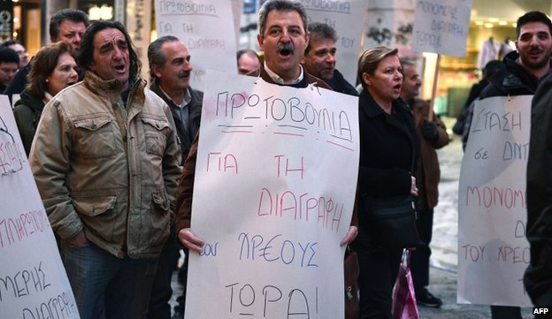 """Public sector worker with placard reading """"Initiative for writing off the debt now"""" - 9 April"""