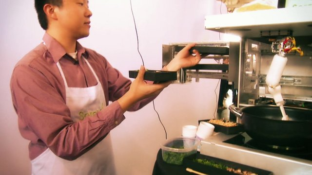 Timothy Chen loads ingredients into the robot chef device Cooki