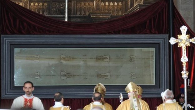 People attend a mass with the Turin Shroud being exhibited inside Turin's cathedral. Photo: 19 April 2015