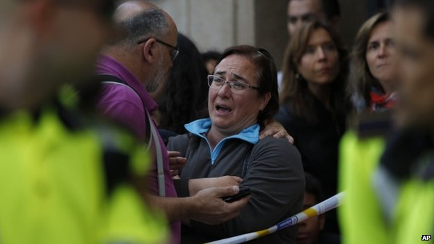 People stand outside a high school in Barcelona, Spain, Monday, April 20, 2015, where a minor has been taken into custody