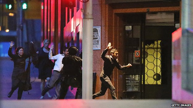 People run with their hands up from the Lindt Cafe, Martin Place during a hostage standoff on December 16, 2014 in Sydney