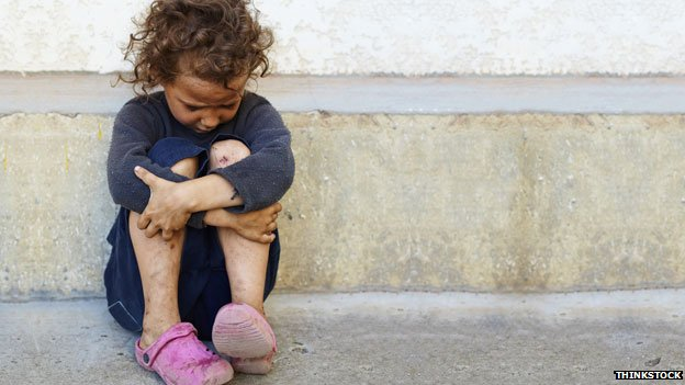 A child sitting on the floor beside a road