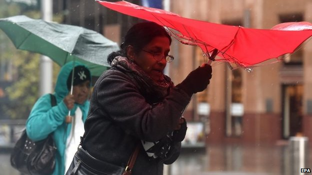 Pedestrians shelter under umbrellas from heavy rain in Sydney, NSW, Australia, 20 April 2015