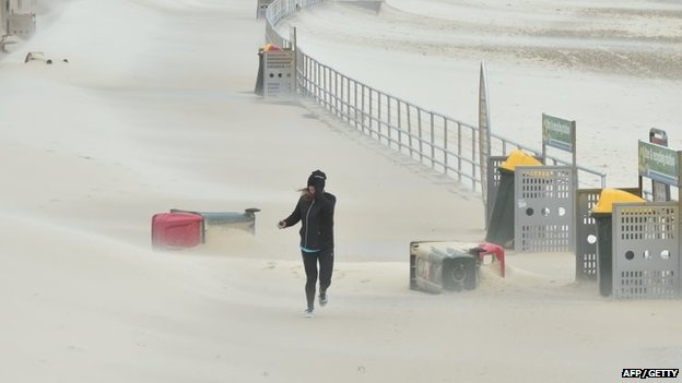 A jogger struggles against sand whipped up by strong winds at Bondi Beach in Sydney on 21 April 2015.