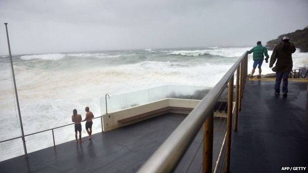 Visitors look out at heavy seas whipped up by strong winds at Bondi Beach in Sydney on 21 April 2015.
