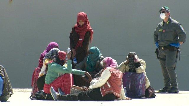 Migrants sit on quay