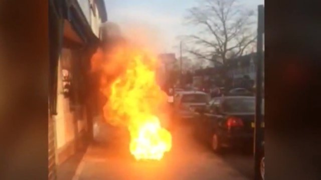Flames shoot out of the manhole in front of shops
