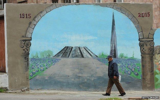 Man walks past mural in Yerevan depicting Armenia's genocide memorial (22 April)