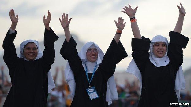 Three nuns waving their arms in the air
