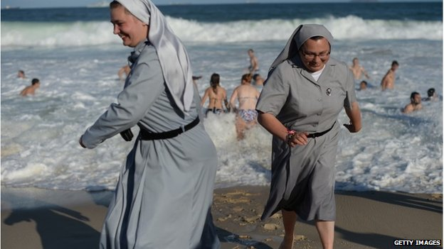 Two Polish nuns running on the beach