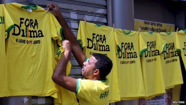 """A vendor hangs shirts reading """"Out, Dilma"""" during a protest against Brazil's President Dilma Rousseff in Sao Paulo on 12 April, 2015."""