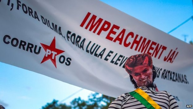 """A dummy wearing a mask depicting Brazilian President Dilma Rousseff as a devil is seen with a sign reading """"Impeachment now!"""" during a protest in Porto Alegre on 12 April, 2015"""