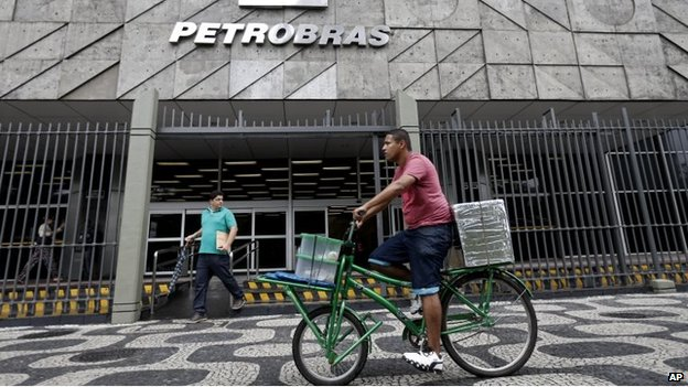 A man rides a bike in front of the Petrobras headquarters in Rio de Janeiro, Brazil, Wednesday, April 22, 2015