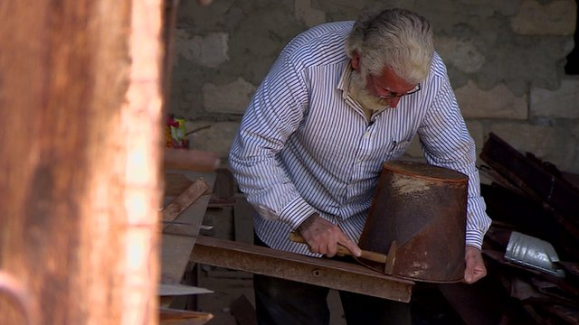 Ara Kashashain, a Syrian Armenian who has settled in Nagorno-Karabakh, repairing a metal bucket