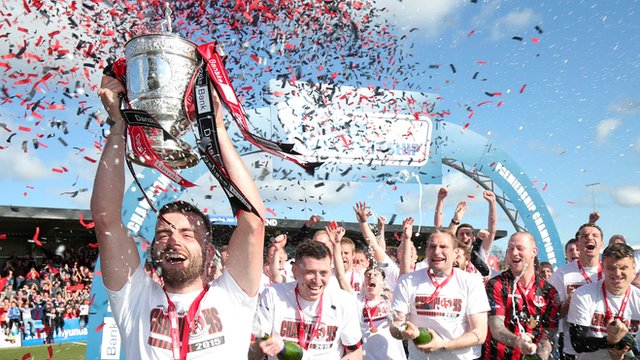 Crusaders captain Colin Coates lifts the Gibson Cup at Seaview