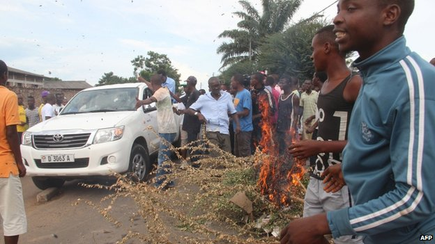 Protesters burn a tree branch within clashes with police in Bujumbura on April 26, 2015