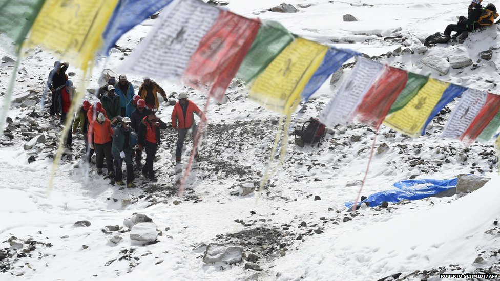 Rescue team personnel carry an injured person towards a waiting helicopter at Everest Base Camp (26 April 2015)