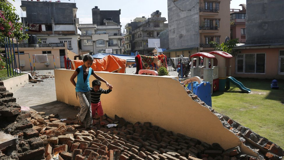 A young girl walks with a boy over a collapsed school playground in Kathmandu (27 April 2015)
