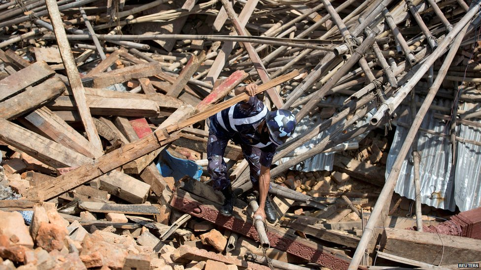 A Nepalese policeman tries to clear the rubble with his hands while looking for survivors at the compound of a collapsed temple in Kathmandu (27 April 2015)