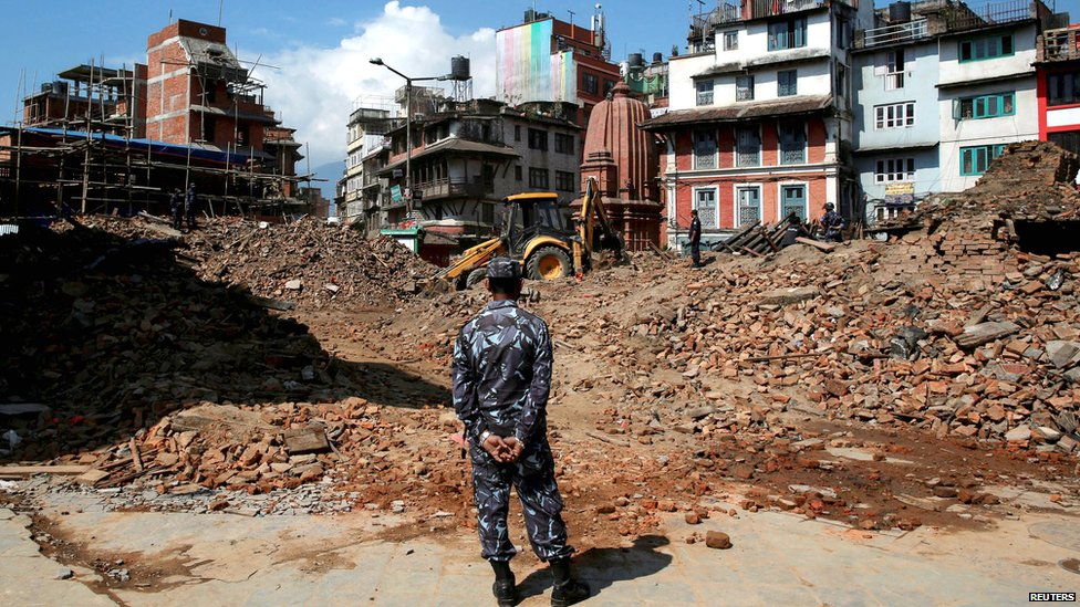A member of Nepalese police personnel looks on as an excavator is used to dig through rubble to search for bodies, in the aftermath of Saturdays earthquake in Kathmandu (27 April 2015)