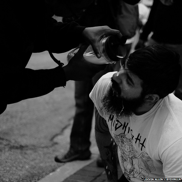 'I'm for the protesters but against the rioters,' Allen says. Underneath this photo of a white protester he wrote: 'He stood on the front lines with us and got pepper sprayed....a brother saw his pain and came to his aid with milk ::::: Deeper than skin and if you stand with us your my brother and or sister idc [I don't care] what color you are'