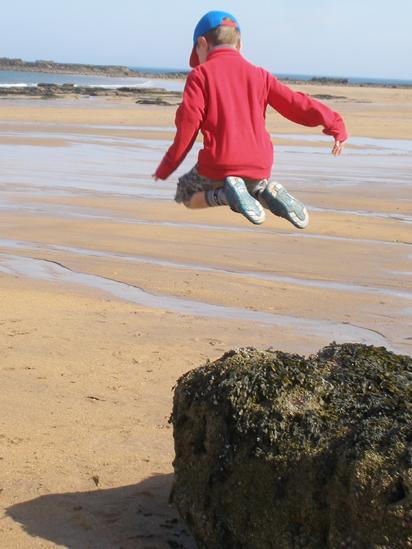 Boy jumping off a rock