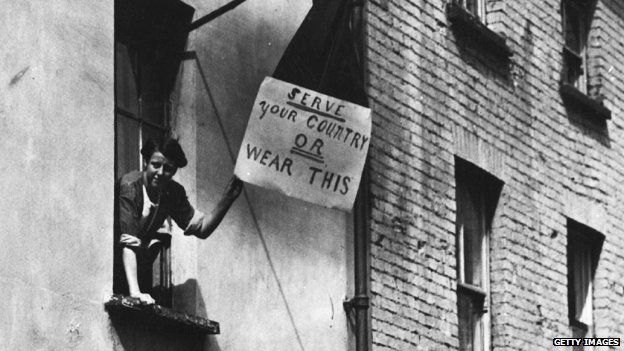 "Woman holds placard which reads: ""Serve your country or wear this"""