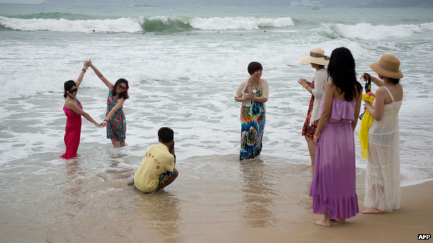 A group of tourists pose for photos in the sea at a beach in the Yalong Bay area of Sanya