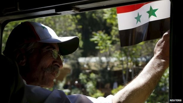 A man holds a Syrian flag on the train in Damascus. Photo: 1 May 2015