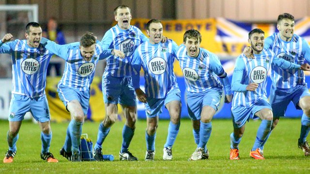 Warrenpoint players celebrate victory in the penalty shootout which guarantees them Irish Premiership football next season