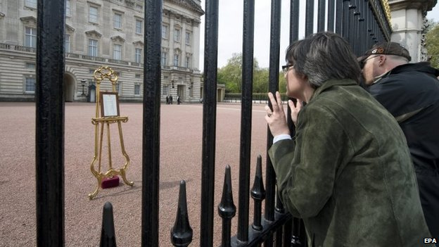 People queue to view the easel containing the announcement of the birth at Buckingham Palace