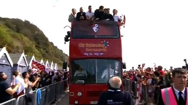 AFC Bournemouth players celebrate winning the Championship title during an open-top bus parade