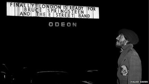 Bruce Springsteen yn edrych ar ei enw ar hysbyseb tu allan i'r Hammersmith Odeon yn Llundain yn 1975 // Bruce Springstein admires his name in lights outside the Hammersmith Odeon in 1975